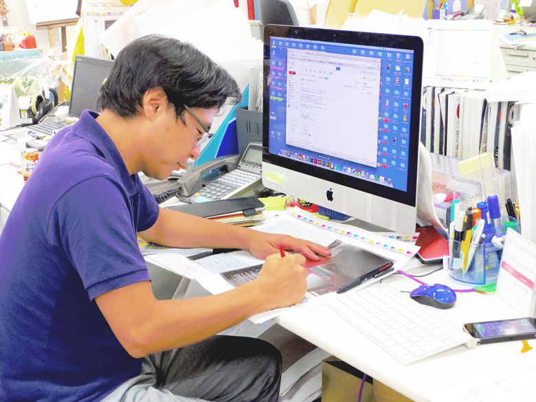 ゲラ(試し刷り)の文字やデザイン、写真等を確認しながら、赤字を入れる八木さん